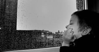 Este niño prefiere mirar por la ventana su aburrido pueblo natal antes que leer tu blog.